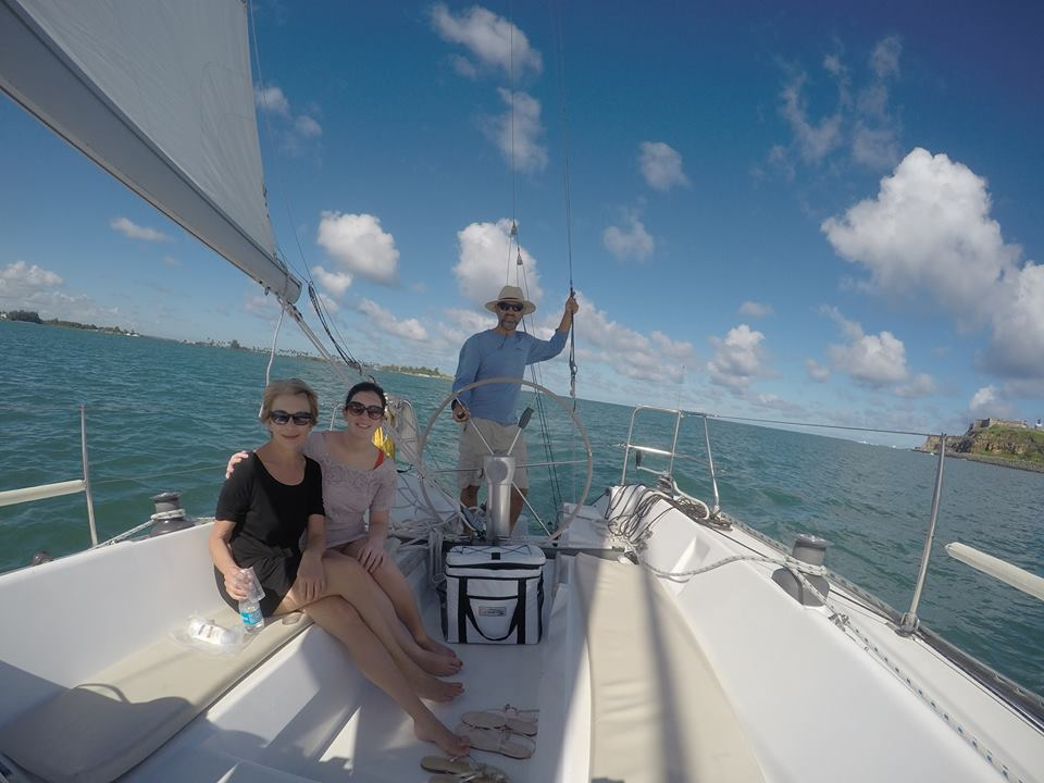 Picture of Captain on sailboat with 2 guests sitting in cockpit sailing under El Morro of San Juan, Puerto Rico.
