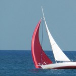 Picture of sailboat with red spinnaker up in light winds on the ocean.