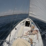 Picture of two guests relaxing in large cockpit of sailboat during daytime sailing.