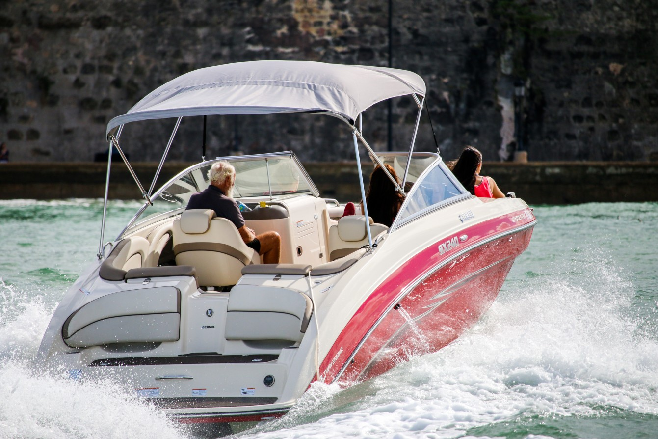 Picture of jetboat going fast with old man, woman driving, and young girl relaxing up front in San Juan Bay.