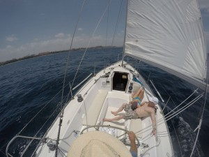 Picture of two passengers relaxing in cockpit of sailboat.